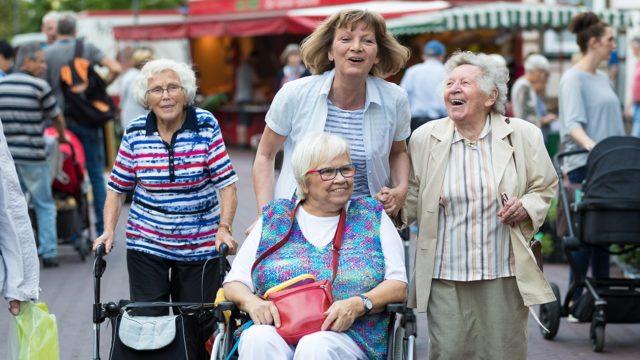 Pflegerin mit drei Damen spazieren lachend über den Wochenmarkt Uelzen