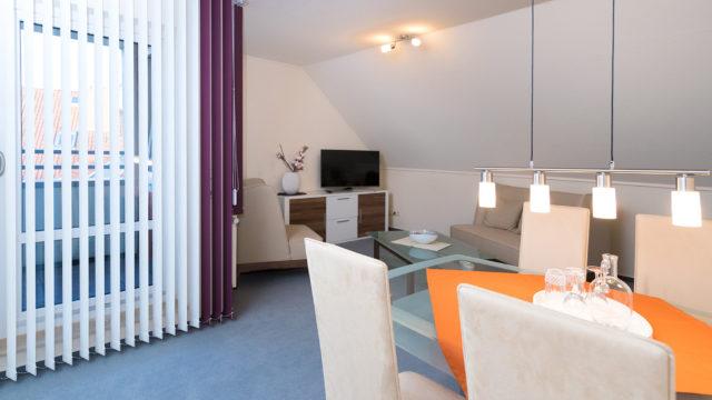 Wohnzimmer mit Fernseher in einem Zimmer mit Balkon im Altenheim Seniorenresidenz Uelzen