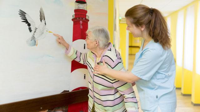 Eine ältere Frau freut mich mit einer Pflegerin über ein Bild im Altenheim Seniorenresidenz Uelzen