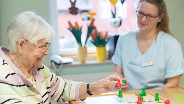 Eine Oma spielt mit einer Pflegerin ein Brettspiel im Eine ältere Frau lacht mit einer Pflegerin im Pflegeheim Seniorenresidenz Uelzen