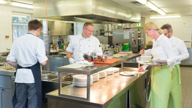 Köche und Servicepersonal bereiten frisches Essen in der Küche im Altenheim Seniorenresidenz Uelzen vor